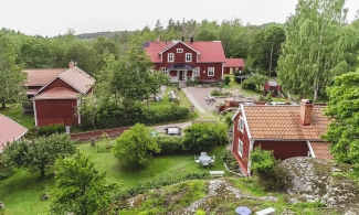 Drone picture at Björkfors Hostel - red houses and white knots