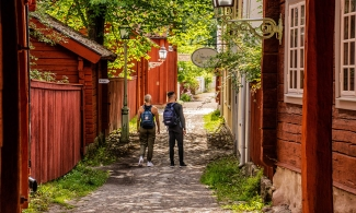 Two people who are out walking in the open-air museum Gamla Linköping and standing in an alley