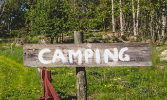 "Picture of a wooden sign where ""Camping"" is written in color"